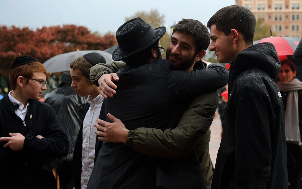 Men greet each other outside the Soldiers and Sailors Memorial Hall before a service to honor and mourn the victims of Saturday's mass shooting at the Tree Of Life Synagogue on October 28, 2018 in Pittsburgh, Pennsylvania. Eleven people were killed and six more were wounded in the mass shooting that police say was fueled by antisemitism. Getty Images