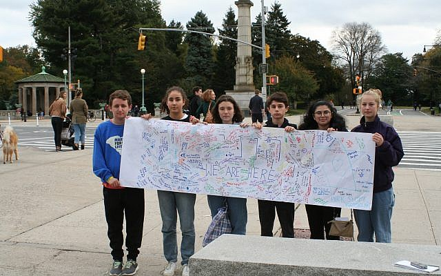 """Teen activists who organized a Sunday afternoon Youth Vigil at Grand Army Plaza hold up a sign for the Pittsburgh community which reads """"Hineni: We Are Here."""" Hannah Dreyfus/JW"""