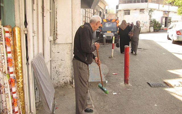 An elderly Shuafat shopkeeper sweeps the street in front of his store. Some residents say they would welcome sanitation services provided by the Jerusalem municipality and not UNRWA, but fear they will be forced to pay high municipal taxes while receiving inferior service. Michele Chabin/JW