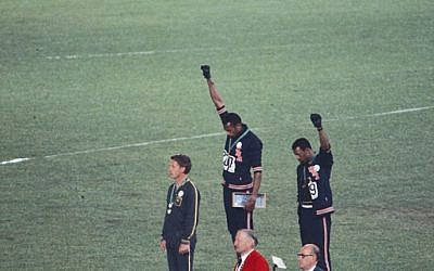 The american sprinters Tommie Smith, John Carlos and Peter Norman during the award ceremony of the 200m race at the Olympic games in Mexico in 1968. During the awards ceremony, Smith and Carlos protested against racial discrimination: they went barefoot on the podium and listened to their anthem bowing their heads and raising a fist with a black glove. Wikimedia Commons