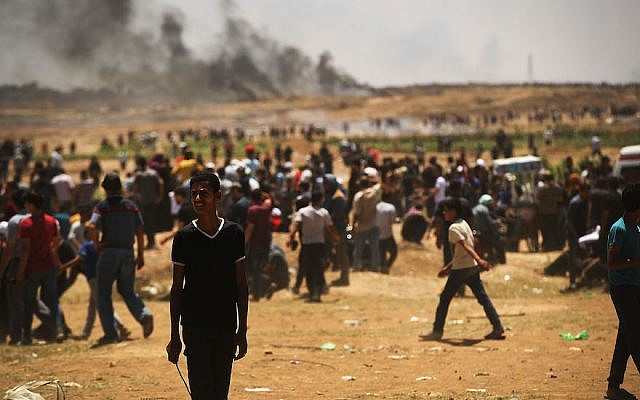 Thousands of Palestinians stand along Gaza's border fence with Israel during mass demonstrations, May 14, 2018. JTA