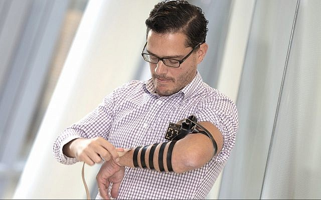 Jack Rubinstein, MD, associate professor in the University of Cincinnati College of Medicine, is shown demonstrating a layman's version of tefillin (Courtesy/ University of Cincinnati)