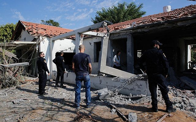 Residents and Israeli police inspect an Ashkelon home damaged Tuesday in a Hamas rocket attack, one of more than 400 rockets that hit southern Israel in the recent escalation. Getty Images
