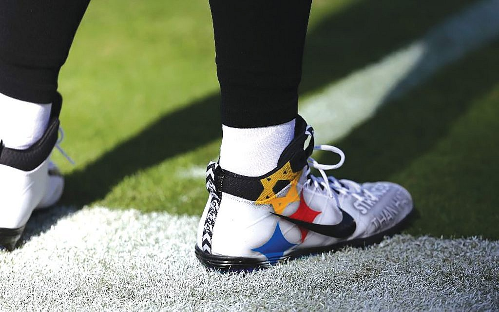 The cleats of Pittsburgh Steelers quarterback Ben Roethlisberger featured a Star of David as part of the Steelers logo during the first game following the Tree of Life killings. GETTY IMAGES