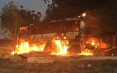 An Israeli bus traveling near the border with Gaza on fire after being hit with Palestinian mortar fire on Nov. 12, 2018. A 19-year-old Israeli man standing next to the bus was seriously injured in the attack. (JTA)