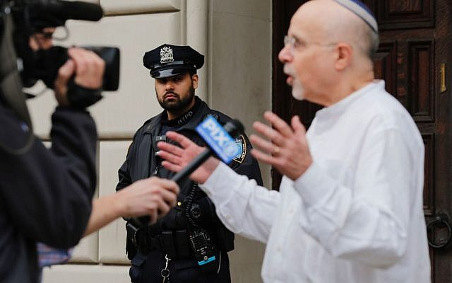 Rabbi Mark Sameth speaks with members of the Media as NYPD officers stand guard at the door of the Union Temple of Brooklyn on November 2, 2018 in New York City. - New York police were investigating anti-Semitic graffiti found inside a Brooklyn synagogue that forced the cancellation of a political event less than a week after the worst anti-Semitic attack in modern US history. Getty Images