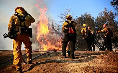 Firefighters battle a blaze at the Salvation Army Camp on November 10, 2018 in Malibu, California. JTA