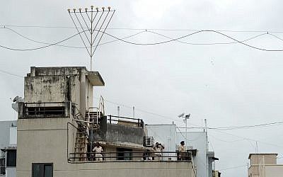 Indian policemen keep watch from atop the refurbished Nariman (Chabad) House after its formal reopening in Mumbai on August 26, 2014. The Jewish centre in Mumbai reopened nearly six years after heavily armed militants stormed the building and killed six people inside during the 2008 attacks on the city. Getty Images
