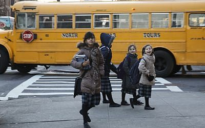 Charedi girls walk past a school bus in Borough Park, one of the sites of the measles outbreak. JTA