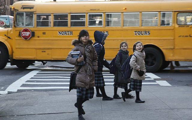 Charedi girls walk past a school bus in Borough Park, one of the sites of the measles outbreak. (JTA)