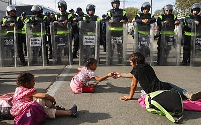 Migrant children play as Mexican riot police look on outside the El Chaparral port of entry in Tijuana, Mexico, Nov. 22, 2018. (JTA)