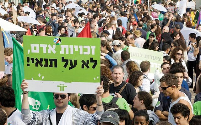 "During a recent rally in Israel, protestors hold signs that read,  ""Human Rights Without Conditions."" Courtesy of ACRI"