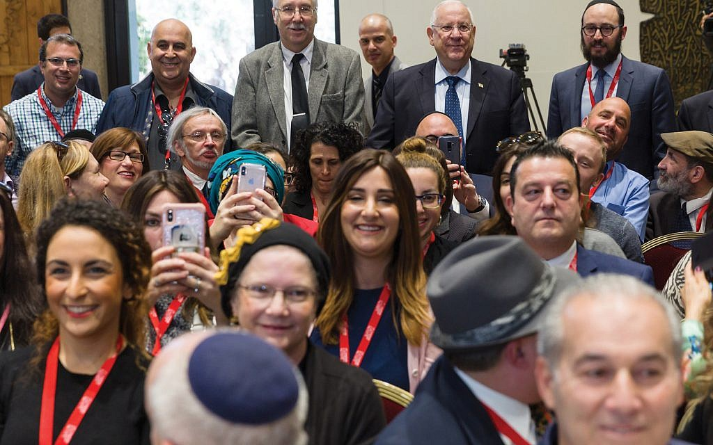 Man of the people: Israeli President Reuven Rivlin (back row, second from right) chose to go to the back of the crowded room to pose with the participants of the Jewish Media Summit at his residence last Wednesday. Courtesy Government Press Office