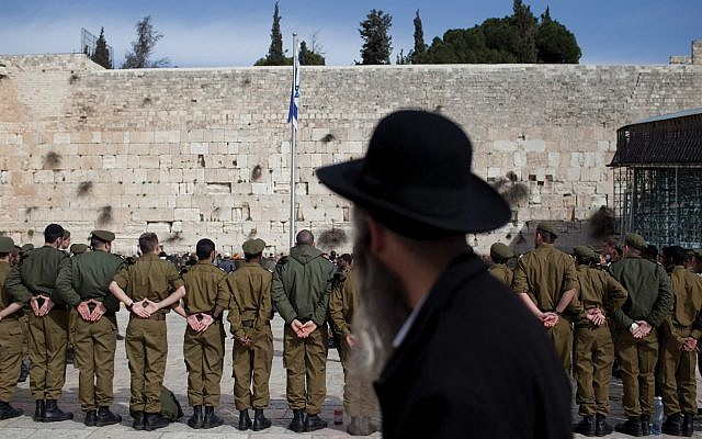 Illustrative photo: A charedi man watches Israeli soldiers at a 2012 army ceremony at the Western Wall.