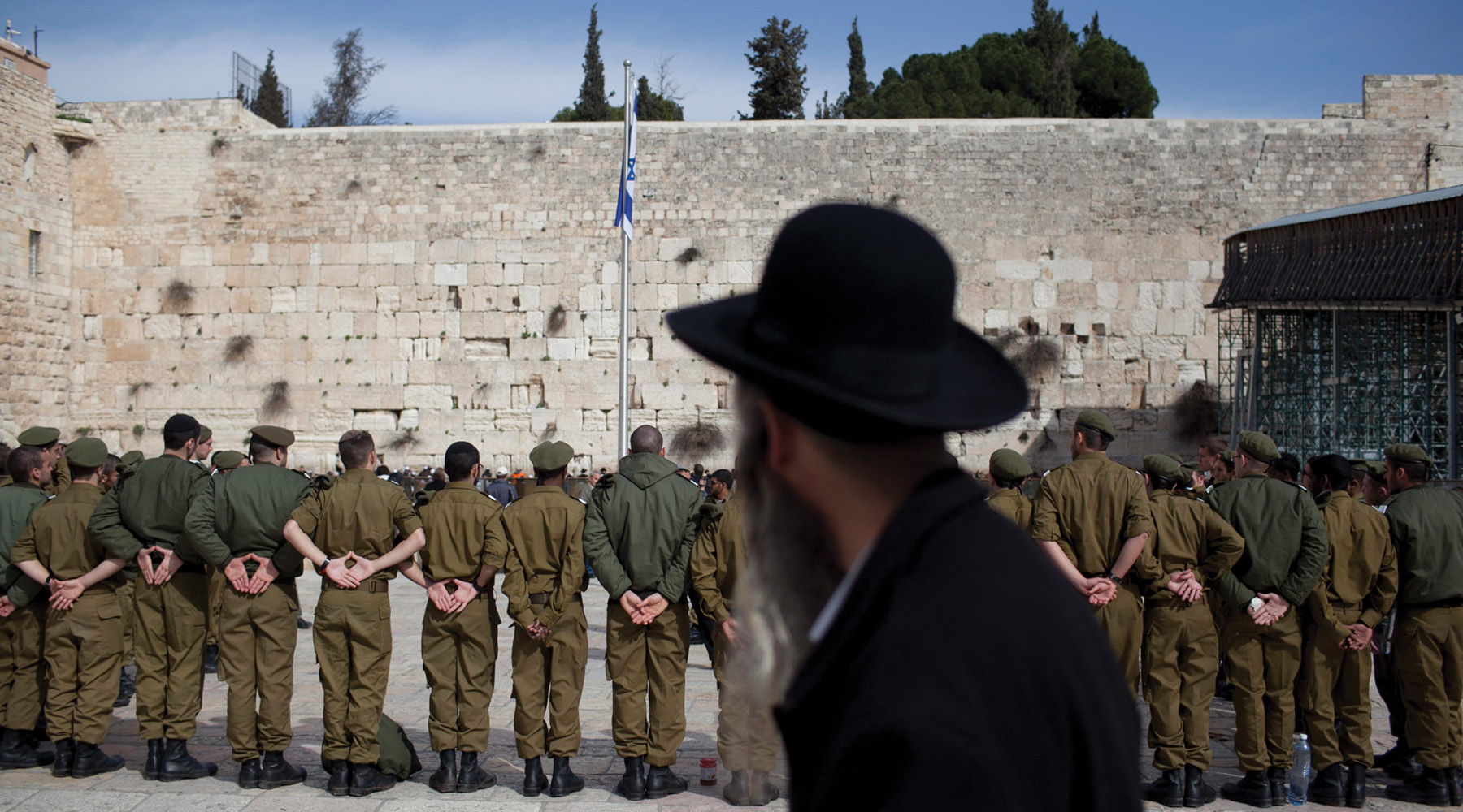 57f07f9de36 Illustrative photo  A charedi man watches Israeli soldiers at a 2012 army  ceremony at the