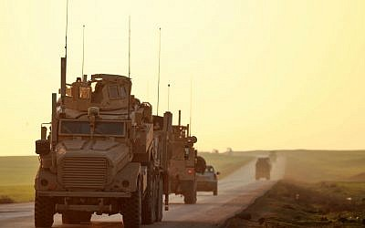 US Marine Corps tactical vehicles are seen driving along a road near the town of Tal Baydar in the countryside of Syria's northeastern Hasakeh province on December 21, 2018. - US President Dnoald Trump said on December 19 that he was ordering a withdrawal of the estimated 2,000 US troops in Syria because IS had been defeated, an assessment rubbished by many, including in his own camp. Getty Images