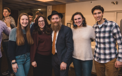 Princeton students enjoy the Chanukah party, along with Chabad Rabbi Eitan Webb and his wife, Gitty (center left). Photo Credit: Nicolas Chae