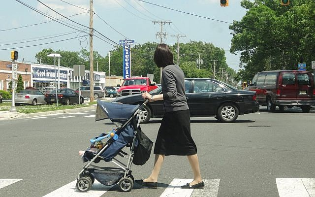 An Orthodox woman pushes a stroller in Lakewood, N.J., in 2013. The population in the largely haredi Orthodox town has boomed in the past couple of decades, and haredi families are looking to move to neighboring towns. (Dennis Fraevich/Flickr) Via JTA