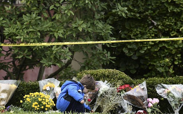 A boy places flowers on October 28, 2018 outside of the Tree of Life Synagogue. BRENDAN SMIALOWSKI/AFP/Getty Images.