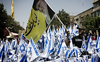 An Iranian man holds a banner bearing a portrait of Iran's supreme leader, Ayatollah Ali Khamenei, above Israeli flagsbefore setting the flags on fire during a demonstration in Tehran on July 25, 2014 to mark the Quds (Jerusalem) Day. BEHROUZ MEHRI/AFP/Getty Images