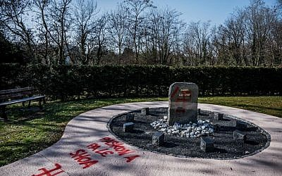 """A photo shows swastikas at the stele of the """"Jardin du Souvenir"""" (Garden of Memories) and the words """"Paskon a pa le shoa"""" a play on words with the holocaust (shoah) sounding in French as """"because we don't have the choice"""" after antisemitic graffiti was discovered in the Champagne-au-Mont-d'Or cemetery on February 20, 2019. Getty Images"""