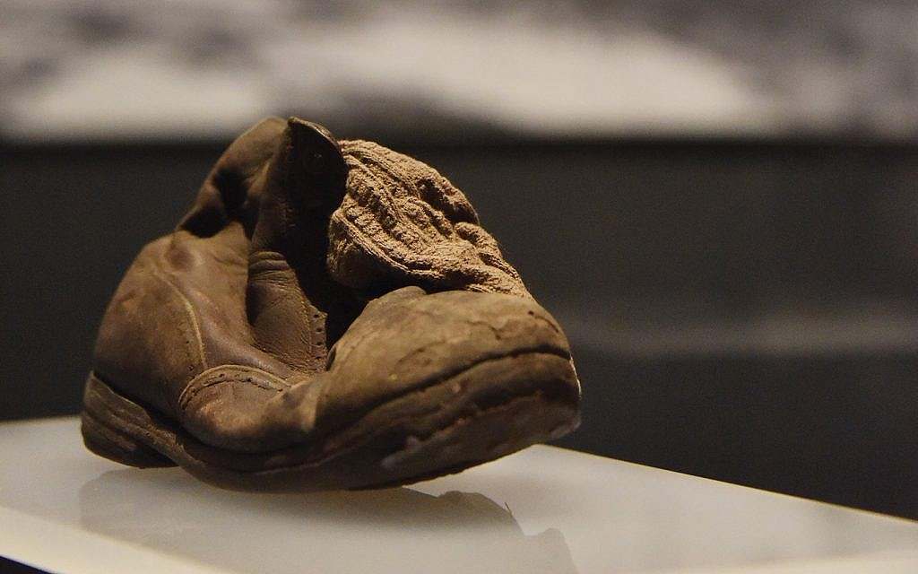 """Photos from the upcoming """"Auschwitz"""" exhibit: A child's shoe and sock with Crematorium IV.  Auschwitz-Birkenau State Museum. ©Musealia"""