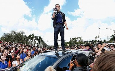 Marjory Stoneman High School student Cameron Kasky addresses area students at a rally at the school after participating in a countywide school walkout in Parkland, Fla., Feb. 21, 2018. (Rhona Wise/AFP/Getty Images/via JTA)