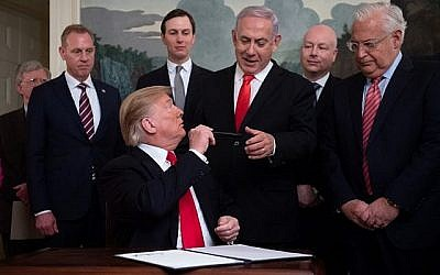 US President Donald Trump hands his pen to Prime Minister Benjamin Netanyahu after signing a Proclamation on the Golan Heights in the Diplomatic Reception Room at the White House, March 25, 2019. (SAUL LOEB/AFP/via Times of Israel)