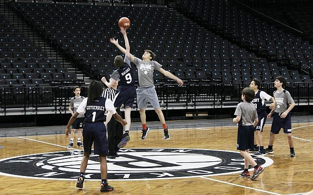 Winners on and off the court: The Solomon Schechter of Manhattan basketball team, in the gray uniforms, won its league championship Sunday at the Barclays Center. PHOTO COURTESY SSSOM