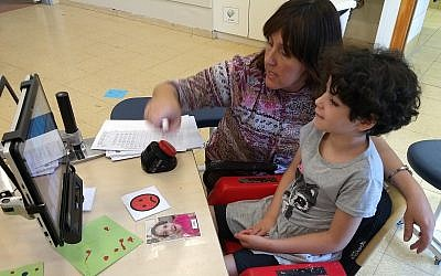 Ayala, 11, a student with a cognitive disability, communicates via a computer screen with her teacher, Rivka Dimant, in a school at Aleh Negev, a campus for Israelis with disabilities. Courtesy of JTA
