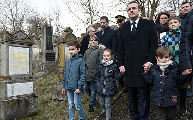 French President Emmanuel Macron (C) holds children by the hands as he walks past graves vandalised with swastikas during a visit at the Jewish cemetery in Quatzenheim. FREDERICK FLORIN/AFP/Getty Images.