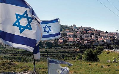 Israeli flags in front of a partial view of the West Bank settlement of Efrat. Israeli sovereignty over the settlements could enflame tensions with American Jews. Getty Images