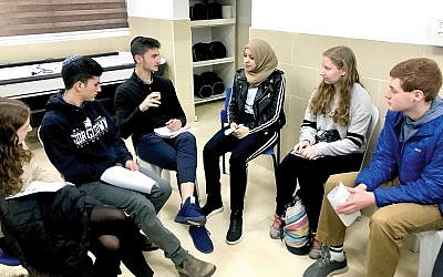 """The author, center, meeting with Arab Israelis on recent Israel trip. He said the trip forced him to realize that he """"harbored too many preconceived notions about both Palestinians and Jewish settlers.""""   Lily Weinberg"""
