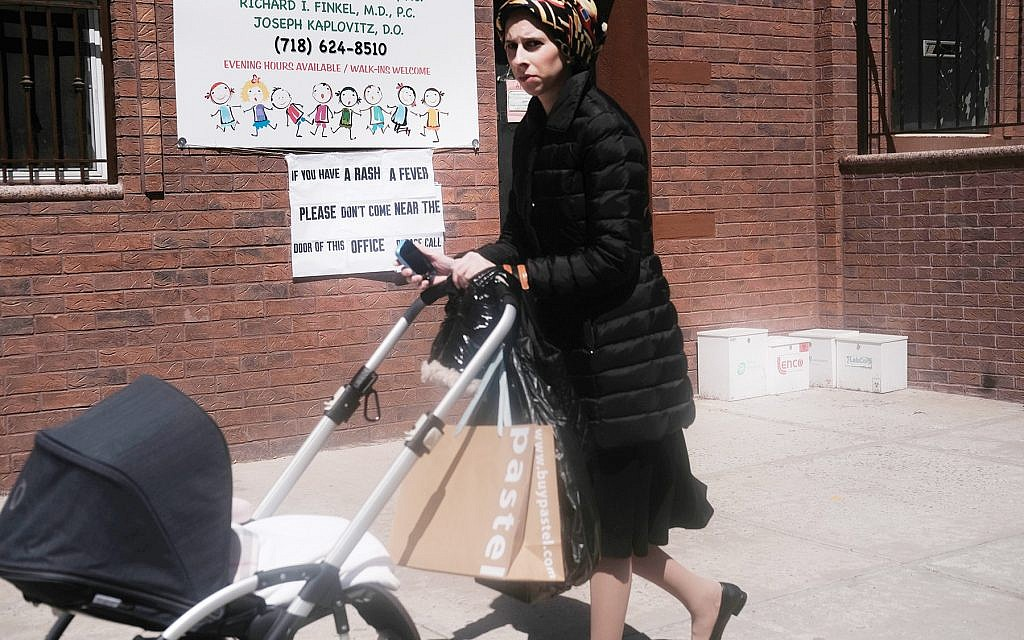 A woman pushes a stroller past a doctor's office in Williamsburg that warns people with rashes or fever not to enter the office. Getty Images