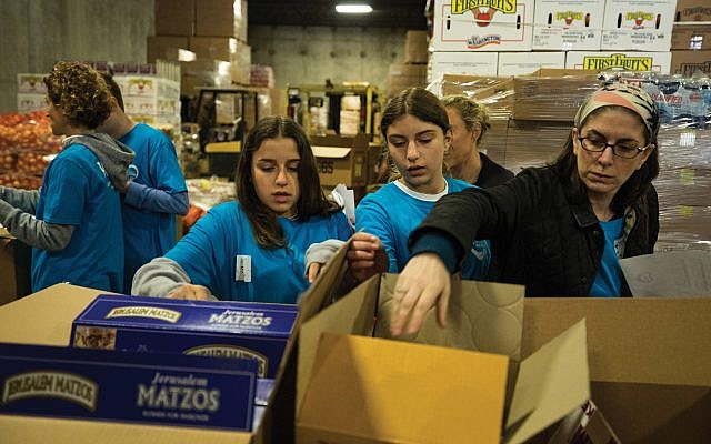 Met Council volunteers pack the tons of kosher-for-Passover goods distributed in the New York area in the weeks before the holiday. Photos courtesy of Met Council