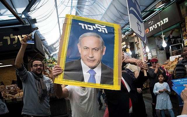 A Likud party supporter holds a picture of Israeli Prime Minister Benjamin Netanyahu on Sunday at the Mahane Yehuda market in Jerusalem. Yonatan Sindel/Flash90