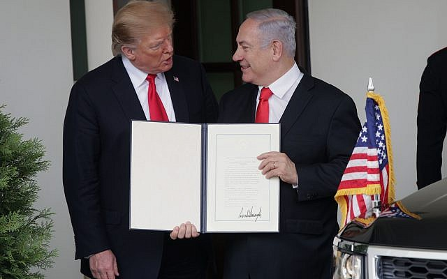 U.S. President Donald Trump (L) and Prime Minister of Israel Benjamin Netanyahu (R) show members of the media the proclamation Trump signed on recognizing Israel's sovereignty over Golan Heights. Getty Images