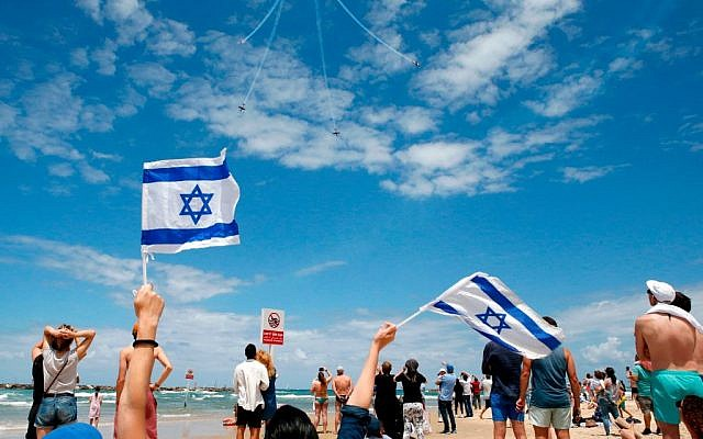 Israelis watch while Efroni T-6 Texan II planes perform during an air show, over the beach in the Mediterranean coastal city of Tel Aviv, on May 9, 2019 as Israel marks its 71st Independence Day. Getty Images