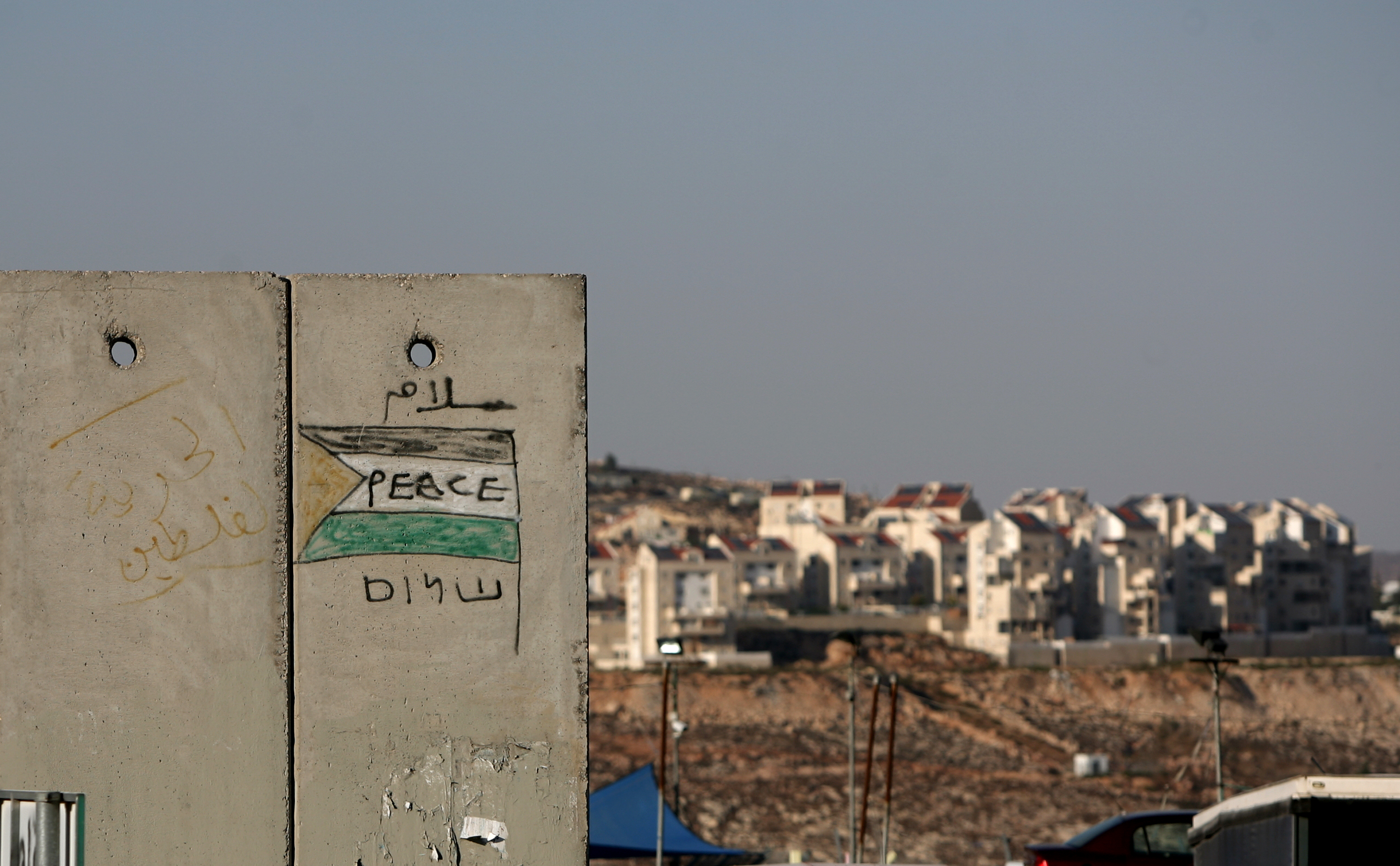 Illustrative image: The Jewish settlement of Kochav Ya'akov is seen behind a section of Israel's separation barrier. Getty Images