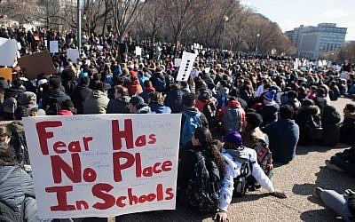 Thousands of local students sit for 17 minutes in honor of the 17 students killed during the Marjory Stoneman Douglas High School shooting, during a nationwide student walkout for gun control in front the White House in Washington, DC, March 14, 2018. SAUL LOEB/AFP/Getty Images