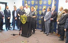 Julie Flaherty, acting police chief of Arlington, Mass., addresses a news conference at the town's police station as Rabbi Avi Bukiet, second from left, looks on, May 17, 2019. Penny Schwartz/JTA