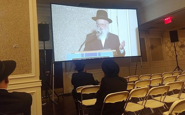 Rabbi Hillel Handler, an Orthodox anti-vaccination leader, speaks via projection screen to an anti-vaccination rally last week at a Jewish wedding hall in Brooklyn. Ben Sales