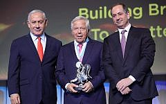 Robert Kraft, center, receives the Genesis Prize at a ceremony in Jerusalem flanked by Israeli Prime Minister Benjamin Netanyahu, left, and Genesis Prize Foundation Chairman Stan Polovets, June 20, 2019. (Natasha Kuperman via JTA)