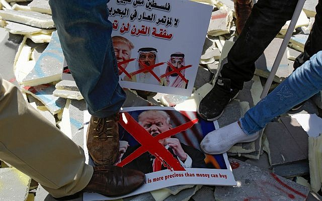 "Palestinians stamp on protest signs showing the crossed-out faces of Israeli Prime Minister Benjamin Netanyahu, US President Donald Trump, King Hamad al-Khalifa of Bahrain, and Saudi Crown Prince Mohammed bin Salman, with a caption above in Arabic reading ""Palestine is not for sale, no to the conference of shame in Bahrain, the deal of the century will not pass."" MUSA AL SHAER/AFP/Getty Images"
