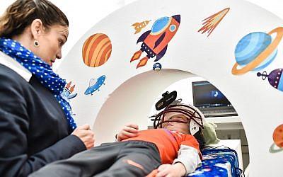 A child tries out a mock MRI machine, designed by Prof. Horowitz-Kraus to prepare children for actual MRI scanning. (Nitzan Zohar)