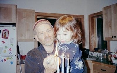 Emma Cohn, as a toddler, lighting Chanukah candles with her father. Photo courtesy of Emma Cohn