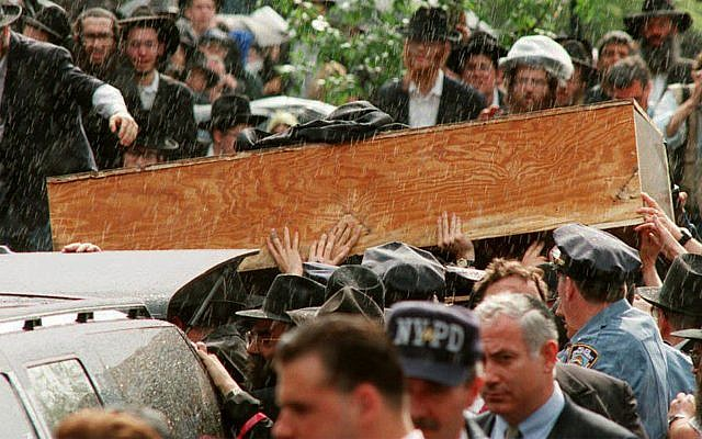 Hands reach out to touch the casket of Rabbi Menachem Schneerson as his funeral procession prepares to leave the world headquarters of the Lubavitch Hasidim in the Crown Heights section of Brooklyn, June 12, 1994. (Mark Phillips/AFP/Getty Images/via JTA)