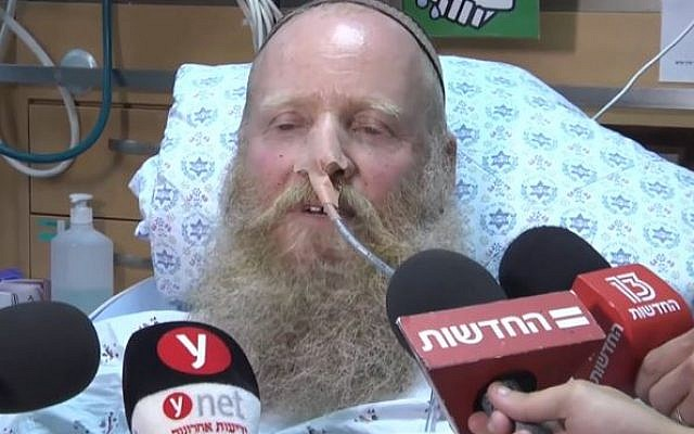 Rabbi Eitan Shnerb speaks to reporters from his hospital bed after being wounded in a terror attack that also killed his daughter Rina and wounded his son Dvir on August 23, 2019 (Screencapture/Ynet/via Times of Israel)