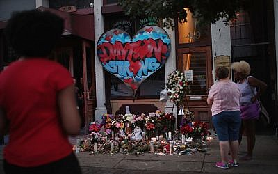 People congregate around a memorial to those killed in Sunday morning's mass shooting in Dayton, Ohio.  Nine people were killed and another 27 injured when a gunman opened fire in a popular entertainment district. Getty Images