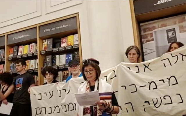 A demonstrator speaks at a Jewish protest against Amazon at one of the company's brick-and-mortar stores in New York City, Aug. 11, 2019. The protest was held on Tisha B'Av, a traditional Jewish day of mourning. Behind the speaker is a banner with a Hebrew quotation from the Book of Lamentations. (Screenshot from Facebook video/via JTA)